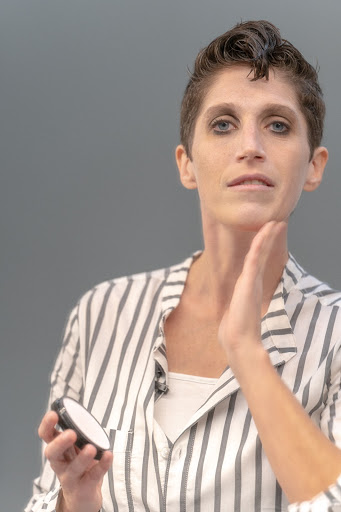 A vertical color headshot of Olivia Scanlon, a white woman with short brown hair, in a grey and white striped button down. She is looking straight at the camera. She holds a makeup compact in her right hand and is touching the side of her chin with her left hand.
