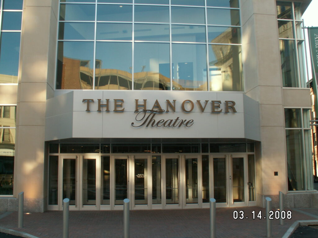 Color photograph of the entrance to The Hanover Theatre. The name is written across the front above multiple sets of doors. The section of the building we see is all windows, with reflections of other buildings in them. The date on the photo reads 03. 14. 2008.