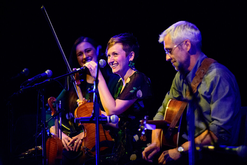 Color photo of three musicians sitting at microphones. The person on the far right is an older white man with short hair and glasses holding a guitar and looking down. The person in the middle is a white woman with short brown hair. She is holding a violin, smiling and looking out to the audience. The person on the left is a white woman with long brown hair. She is out of focus and looks smiling at the woman in the middle.
