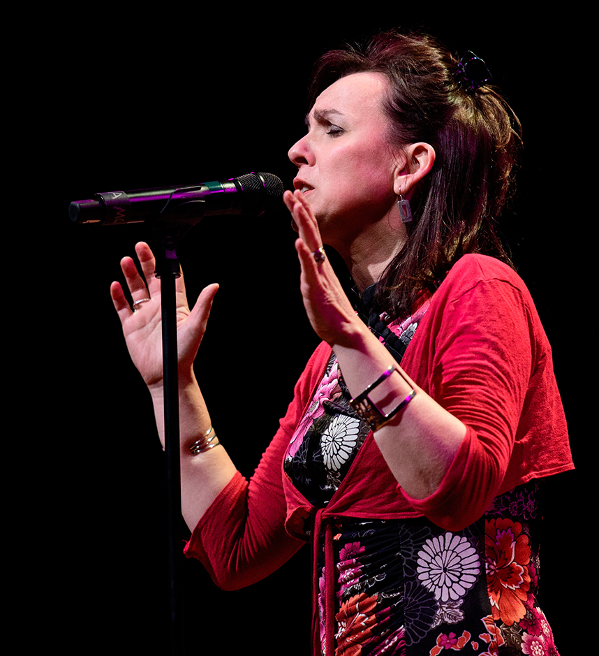 A color photo of a white woman with shoulder length brown hair that's half up. She is singing into a microphone with her hands in the air, animated. She wears a black dress with a brightly colored floral pattern and a cropped tie front red sweater. She has a big bangle bracelet on each wrist.