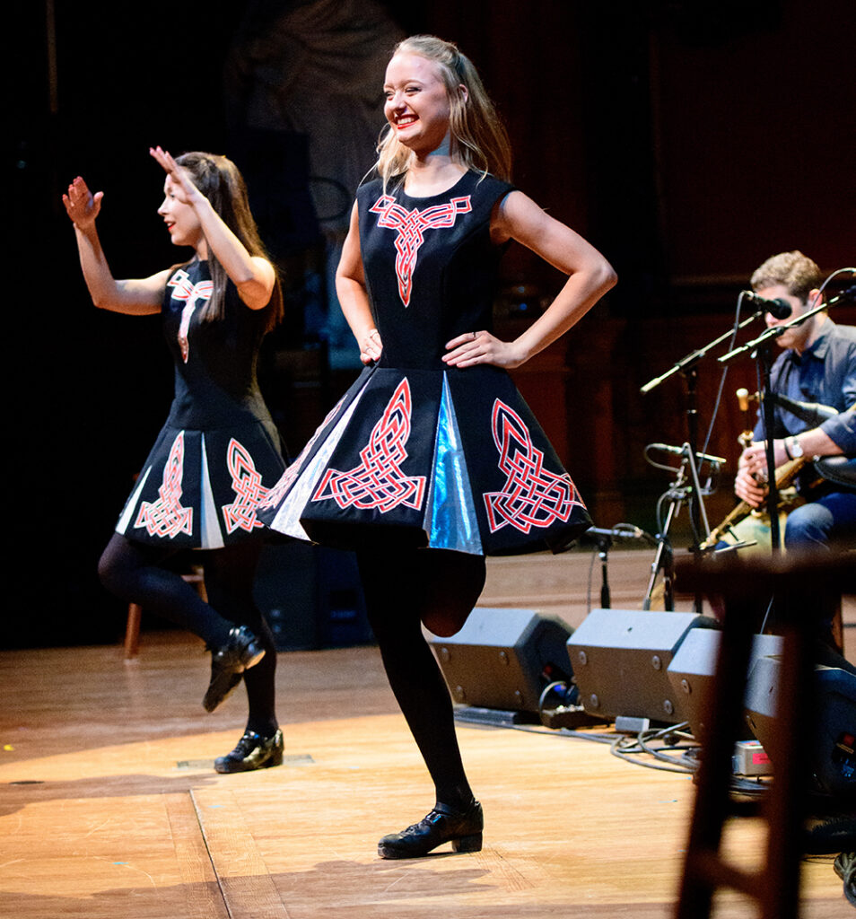 A color photograph of two girls dancing and smiling. They both are caught mid-movement with a foot off the ground. The one closer to the camera has her hands on her hips, the other has her hands raised in the air. They wear short sleeved black dresses with full, knee-length skirts and red Celtic knot patterns on them.