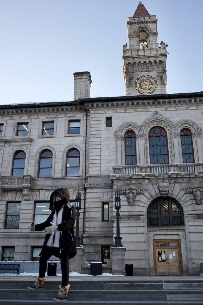 Color photograph of city hall. Olivia Scanlon stands on the steps in winter clothing and a mask, holding her her hands out in front of her, animated.