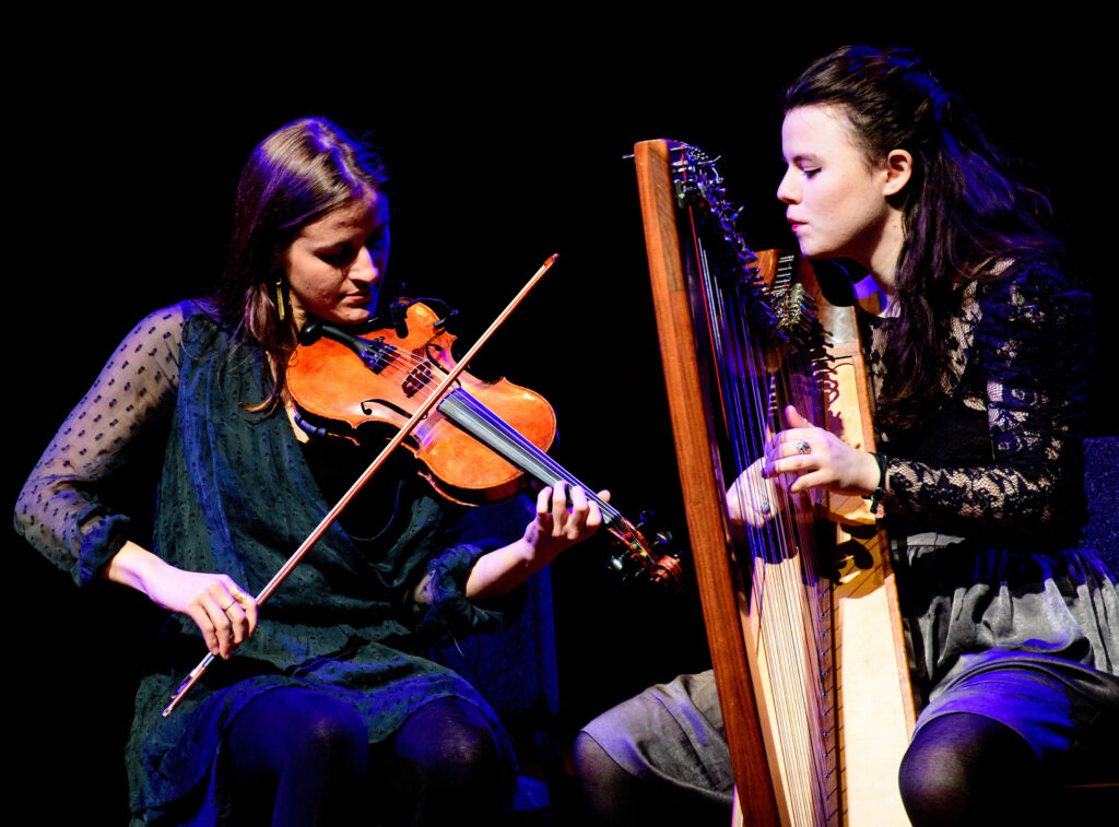 A color photograph of two women with brown shoulder length hair. The woman on the left wears a loose dark green knee length dress with sheer long sleeves and plays the violin. The woman on the left wears a black long sleeve lace top and a grey knee length skirt and black nylons. She plays a harp.