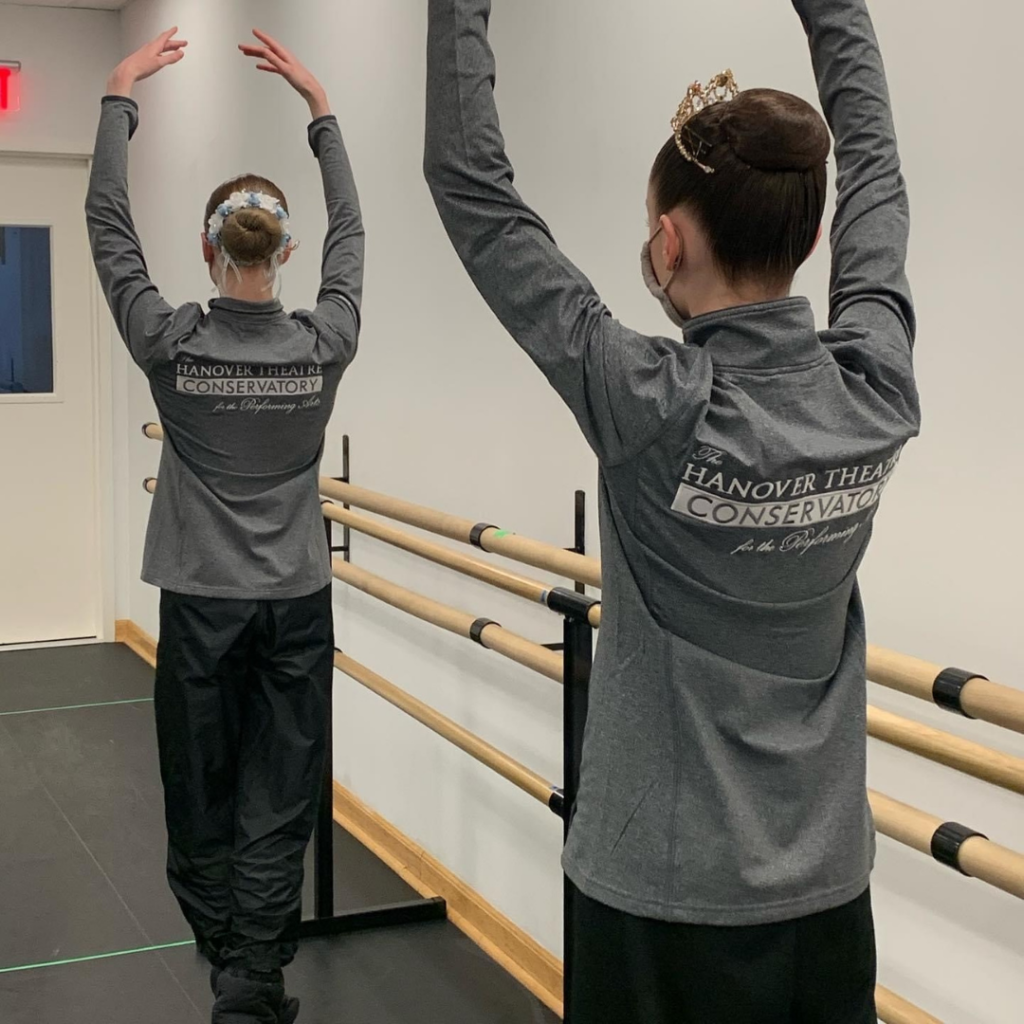 A color image of two dancers in a dance studio. They each have their hair up in a neat bun and their backs are to the camera. They are wearing warmup clothes and their jackets read Hanover Theatre Conservatory for the Performing Arts. They are in fifth position with their arms over their heads.