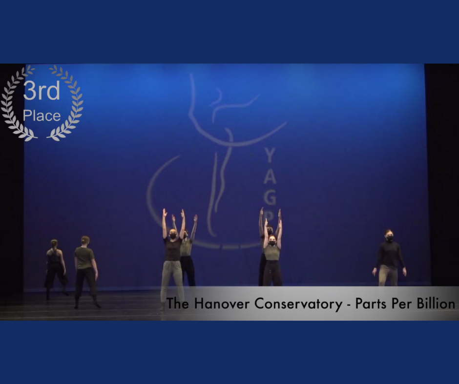 """Color photograph of the YAGP stage as the dancers perform the ensemble piece. They are dressed in black and grey. The four dancers in the middle stand with their arms straight over their head. There is a 3rd Place insignia over the top left of the photo and the bottom reads """"The Hanover Conservatory - Parts Per Billion""""."""