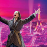 Color image of the character of Anastasia with arms outstretched, mouth open in song in front of a pink background of the city of Paris and the Eiffel Tower.