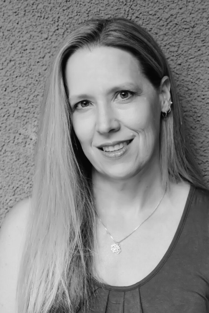 Black and white headshot of Kate, a white woman with long hair. Kate is smiling as she looks into the camera.