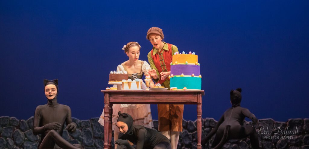 Students performing Hansel and Gretel. Hansel and Gretel stand at a table covered in cakes while actors playing cats surround them on the ground.