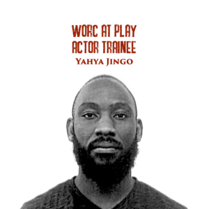 """Black and white headshot of Yahya, a young black man with a mustache and beard looking straight into the camera. Red text on the top of the photograph reads """"Worc At Play Actor Trainee Yahya Jingo""""."""