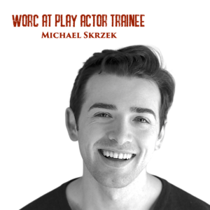"""Black and white headshot of Michael, a young white man with short hair. He is smiling as he looks into the camera. Red text on the top of the photograph reads """"Worc At Play Actor Trainee Michael Skrzek""""."""