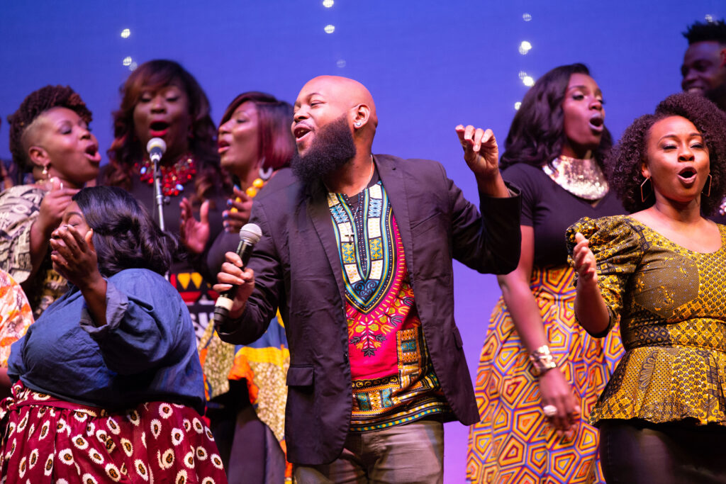 Trey McLaughlin and The Sounds of Zamar are joyfully singing with their arms raised.