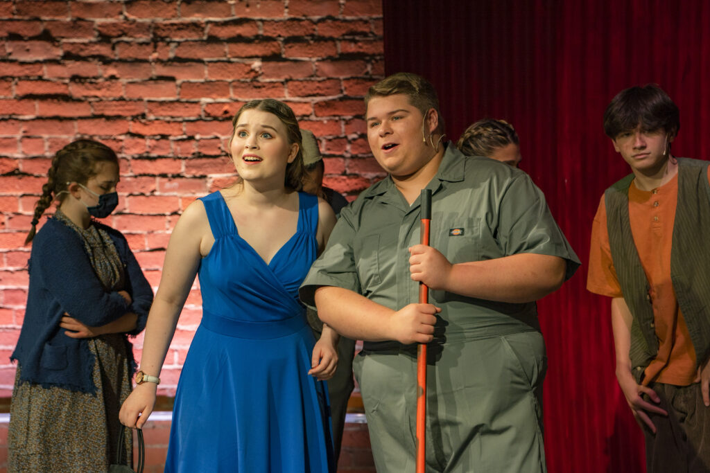 Heather Bachand and Dylan Morin, two students from the Youth Acting Company's production of Urinetown, are standing together, looking into the distance as they sing in front of a red cutain and the brick wall of the Brick Box Theater. Other cast members are passing behind them. Heather is wearing a simple blue dress and Dylan is wearing green coveralls with a broom handle in his hands.