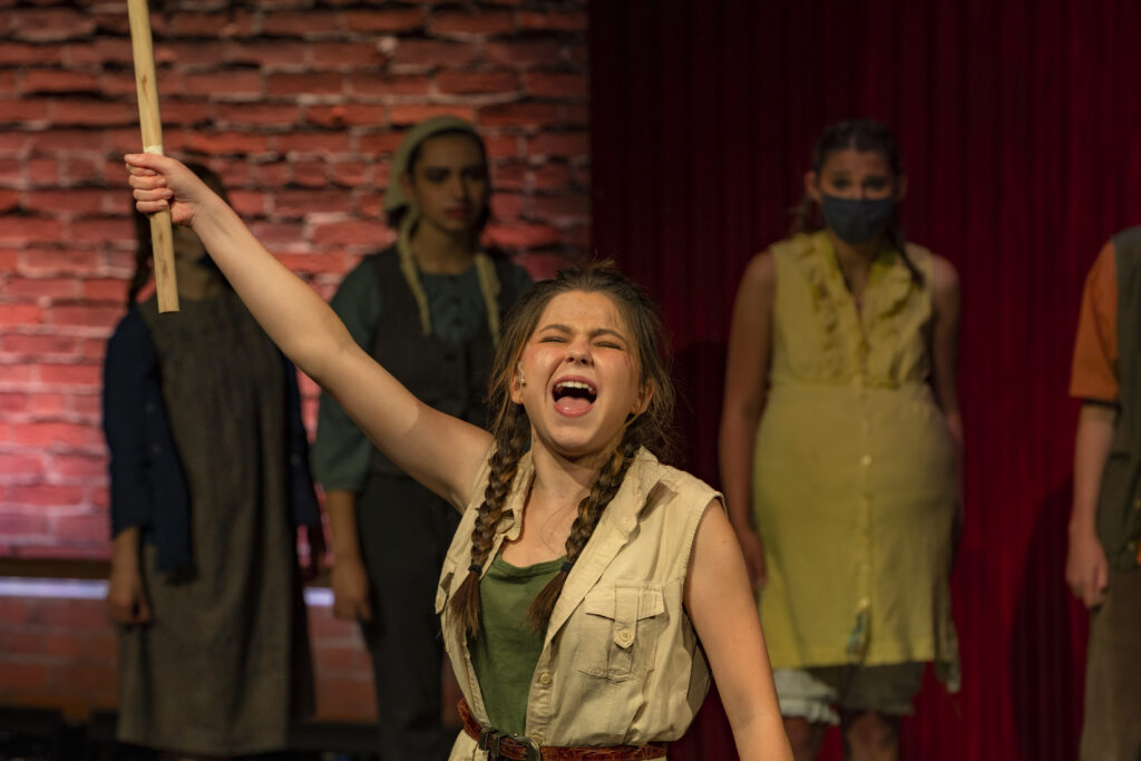 Perry Drugan, a student from the Youth Acting Company's production of Urinetown, is belting a song as she holds up a plunger. Her eyes are shut and her face is clenched as she sings. She is wearing a green shirt and a tan vest.
