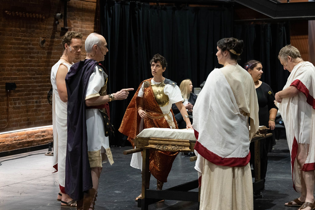 A few Julius Caesar Cast members are standing in the Brick Box Theater, working on a scene. Liv Scanlon, Brandon Grimes, Dale Place, Lia Madeline and Steven Barkhimer are standing in front of the platform that Caesar's body will be carried away on in the show. They are all in full costume, in long flowing Roman garb.