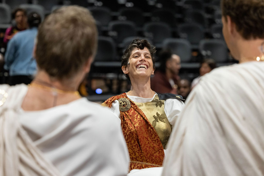 Liv Scanlon, a white woman with short curly brown hair, is standing in front of two Julius Caesar cast members. She in full costume, with a gold chest plate and a red cape. Her head is tossed back, mid laugh as she chats with actors in the JMAC Brick Box Theater.