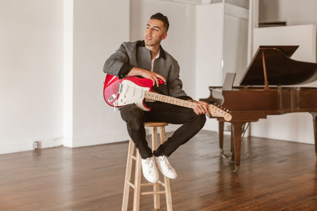 Ricky Duran is sitting on a wooden stool, dressed in white shoes, dark jeans and a grey blazer. He's holding a red bass guitar as he looks off camera. There is a piano in the background.