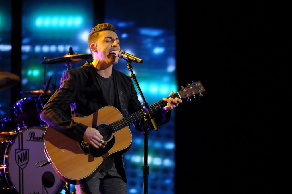 """Ricky Duran is performing on """"The Voice"""" stage in front of a blue screen and a drum set. He is wearing a black blazer, a black t-shirt and dark jeans. He is holding an acoustic guitar as he sings into a microphone."""