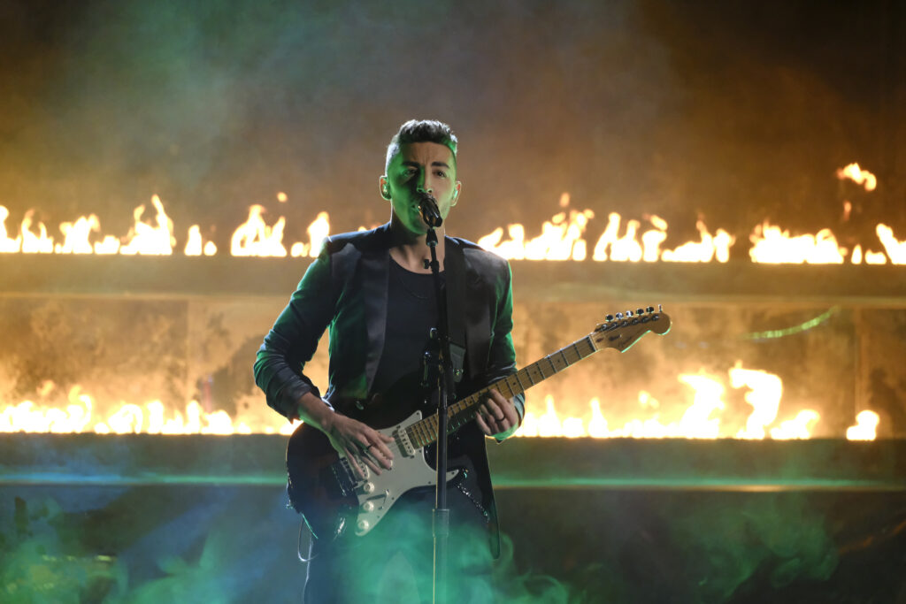 """Ricky Duran is performing on """"The Voice"""" stage in front of two lines of fire. He is wearing an all black suit  and holding a black bass guitar as he sings into a microphone."""